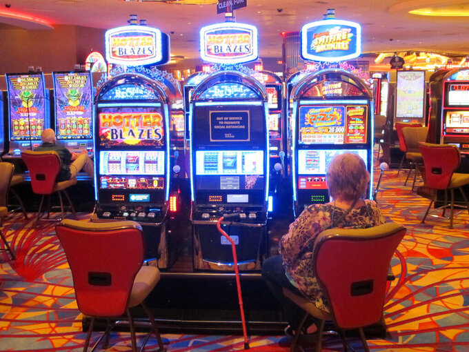 This May 3, 2021 photo shows a woman playing a slot machine at the Hard Rock casino in Atlantic City N.J. On Monday, May 24, 2021, New Jersey gambling regulators released figures showing that the Atlantic City casinos' first quarter earnings more than tripled this year compared to the same period last year, when the COVID19 pandemic wiped out half of March.(AP Photo/Wayne Parry)