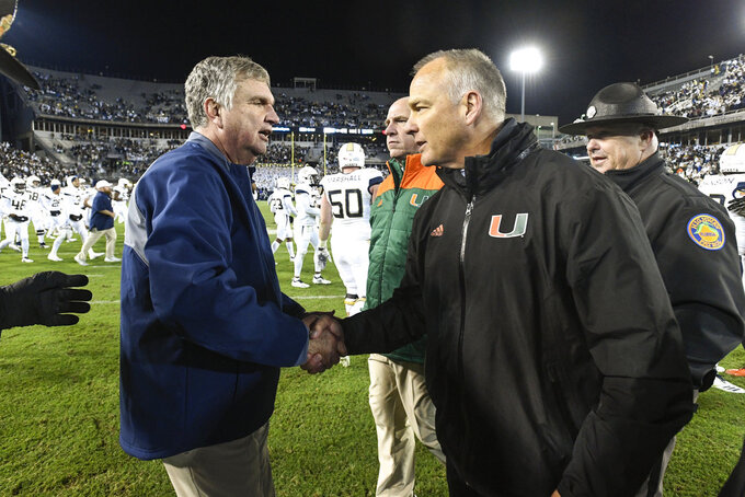 Georgia Tech coach Paul Johnson, left, and Miami coach Mark Richt meet at midfield after an NCAA college football game Saturday, Nov. 10, 2018, in Atlanta. Georgia Tech won 27-21. (AP Photo/John Amis)