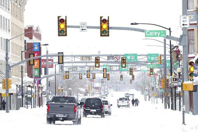 """FILE - In this March 15, 2021 file photo, cars and pedestrians travel down West Lincoln way in downtown Cheyenne, Wyo., on Monday, March 15, 2021. Lawmakers are trying to stop 144 cities across the U.S. from losing their designations as """"metropolitan areas"""" because the federal government is upgrading the standard from a minimum of 50,000 residents in its core to a minimum of 100,000 people. Cheyenne is among the cities at risk of losing the designation (Michael Cummo/The Wyoming Tribune Eagle via AP, File)"""
