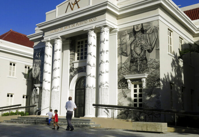 Visitors walk into the Museum of Art ahead of the announcement by Google Arts & Culture that it digitized more than 350 artworks in San Juan, Puerto Rico, Thursday, Nov. 7, 2019. (AP Photo/Dánica Coto)