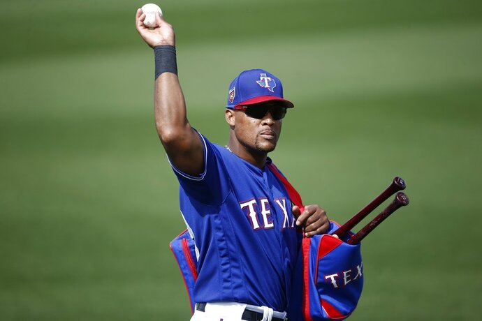 Texas Rangers third baseman Adrian Beltre tosses a baseball to a fan during the fifth inning of the team's spring training baseball game against the Chicago White Sox on Thursday, March 8, 2018, in Surprise, Ariz. Going into his 21st big-league season, Beltre is one of only two current players who have played at least 20 MLB seasons.(AP Photo/Ross D. Franklin)