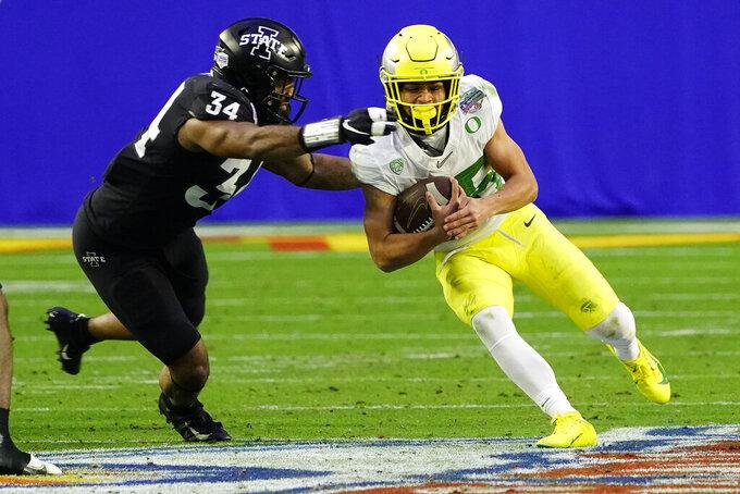 Oregon running back Travis Dye is hit by Iowa State linebacker O'Rien Vance (34) during the second half of the Fiesta Bowl NCAA college football game, Saturday, Jan. 2, 2021, in Glendale, Ariz. (AP Photo/Rick Scuteri)