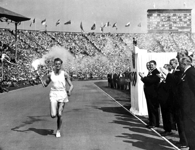 FILE - In this July 29, 1948 file photo, British athlete John Mark holds the Olympic Flame aloft as he makes his circuit of the Olympic track during the opening ceremony of the XIV Olympiad, in Wembley Stadium, London. London was still cleaning up bombing damage from World War II when it staged the Olympics in 1948. Britain was also struggling financially; food, clothing and gas were still being rationed. The athletes had to bring their own towels and, with housing in short supply, were accommodated in schools and Royal Air Force camps. The games were organized in less than two years, and despite the tiny budget it was a success, its legacies including greater sporting opportunities for women. (AP Photo, File)