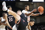 Vanderbilt's Maxwell Evans, top right, passes the ball as South Carolina's Maik Kotsar (21) tumbles into him in the first half of an NCAA college basketball game Saturday, March 7, 2020, in Nashville, Tenn. (AP Photo/Mark Humphrey)