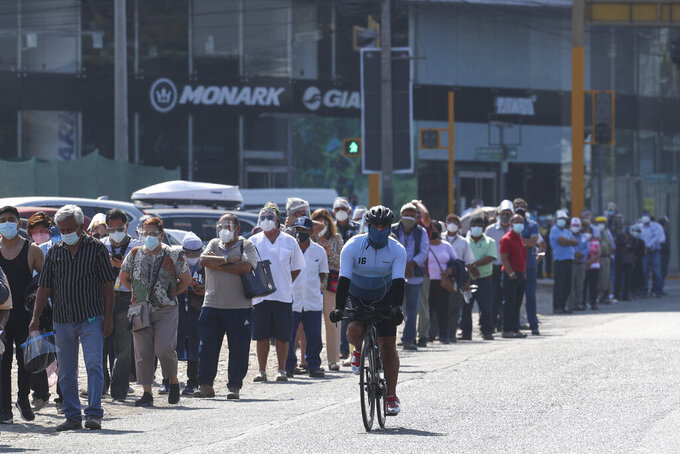 A cyclist pedals along voters wearing masks to curb the spread of the new coronavirus lining up to enter a polling station during general elections in Lima, Peru, Sunday, April 11, 2021. (AP Photo/Martin Mejia)