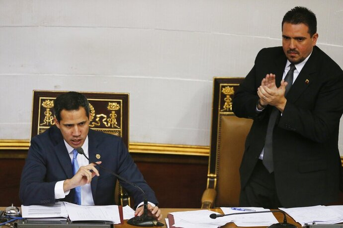 Venezuelan opposition leader and self-proclaimed interim president of Venezuela Juan Guaido, left, speaks as National Assembly Second Vice President Stalin González applauds him during the body's weekly session in Caracas, Venezuela, Tuesday, Sept. 17, 2019. Venezuela's opposition-led congress has again thrown its support behind Guaidó, saying he'll serve as the crisis-wracked nation's interim president until they've ended Nicolás Maduro's grip on power. (AP Photo/Ariana Cubillos)