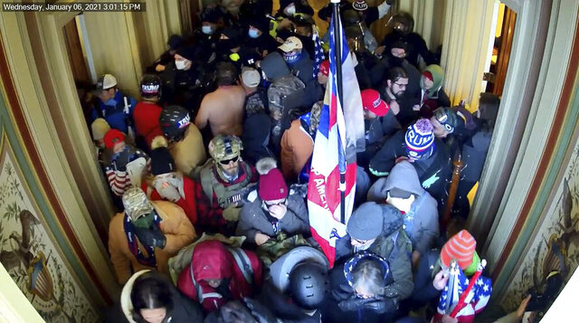 This image provided by the FBI taken from a video security camera in the U.S. Capitol building on Jan. 6, 2021, shows a man wearing a Trump 2020 winter cap and a bullet proof vest beside a wooden coat rack, standing among other rioters. The FBI identified the man as Dustin Thompson. Federal authorities say Thompson illegally entered the U.S. Capitol on Jan. 6 and while he was there stole the coat rack. (The FBI via AP)