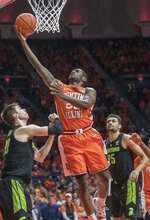 Illinois guard Da'Monte Williams (20) goes up with a shot between Michigan State guard Matt McQuaid (20) and forward Kenny Goins (25) during the first half of an NCAA college basketball game in Champaign, Ill., Tuesday, Feb. 5, 2019. (AP Photo/Rick Danzl)