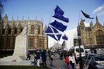 A Scottish flag, center bottom, is held up alongside European flags by protestors who support Britain remaining in the European Union across the street from the Houses of Parliament in London, Tuesday, March 5, 2019. The Scottish Parliament and the National Assembly for Wales are both due to vote later Tuesday on motions declaring opposition to British Prime Minister Theresa May's Brexit deal and declare their opposition a no-deal Brexit. (AP Photo/Matt Dunham)