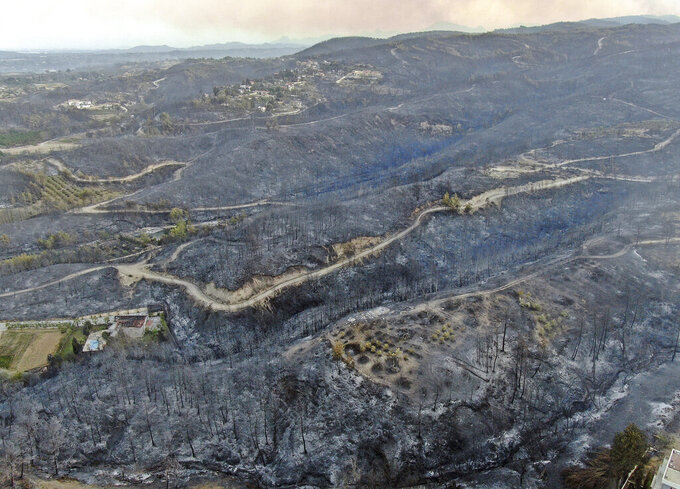 An aerial photo shows destroyed houses in a village as wildfire continue to rage the forests near the Mediterranean coastal town of Manavgat, Antalya, Turkey, Thursday, July 29, 2021. Authorities evacuated homes in southern Turkey as a wildfire fanned by strong winds raged through a forest area near the Mediterranean coastal town of Manavgat. District governor Mustafa Yigit said residents of four neighborhoods were moved out of the fire's path as firefighters worked to control the blaze that broke out Wednesday. It was not immediately clear what caused the fire but authorities said nearby tourist resorts were not affected. (Suat Metin/IHA via AP)