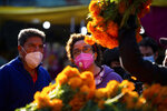 Customers, wearing protective face masks amid the new cornavirus pandemic, shop for flowers at the Jamaica Market, in Mexico City, Thursday, Oct. 29, 2020. Mexico's Day of the Dead celebration this weekend won't be the same in a year so marked by death, in a country where more than 90,000 people have died of COVID-19. Many of those had to be cremated rather than buried, and even for those with gravesides to visit, the pandemic has forced authorities in most parts of Mexico to close cemeteries to prevent the traditional Nov. 1-2 observances when entire families clean and decorate tombs. (AP Photo/Fernando Llano)