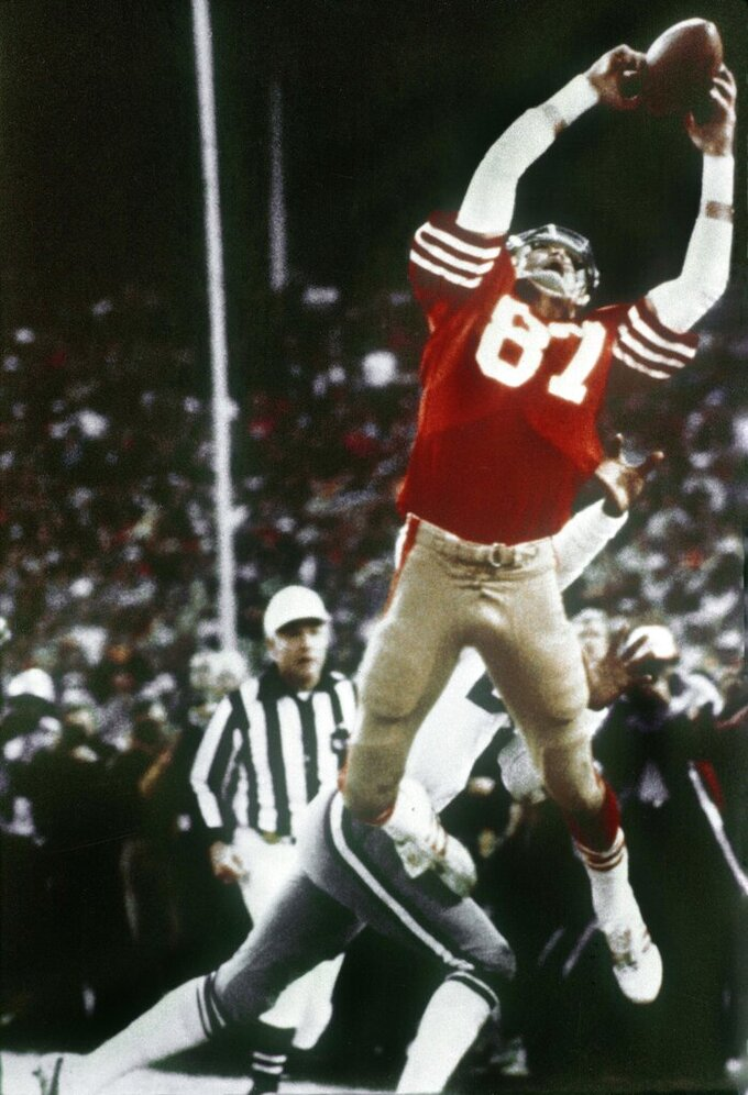 "FILE - In this Jan. 10, 1982, file photo, San Francisco 49ers wide receiver Dwight Clark makes ""The Catch,"" on a pass from Joe Montana that tied the game late in the fourth quarter against the Dallas Cowboys in the NFC championship football game at Candlestick Park in San Francisco. A pair of Super Bowl winning teams that launched dynasties in San Francisco and New England highlighted the list of the NFL's greatest teams, numbers 31-100. Coming in at No. 31 was the 1981 San Francisco 49ers led by coach Bill Walsh and quarterback Joe Montana. (AP Photo/Dallas Morning News, Phil Huber, File)/The Dallas Morning News via AP)/The Dallas Morning News via AP)"