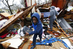 Emma Carter's grandsons comb the remains of her mobile home in Pickens, Miss., looking for salvageable clothing and personal items after severe weather hit the area, Thursday, Feb. 6, 2020. None of the other mobile homes adjacent to the Carter's were destroyed when the winter storm hit Wednesday. (AP Photo/Rogelio V. Solis)
