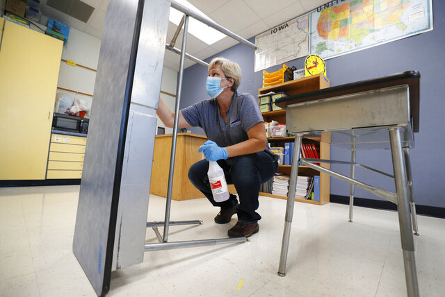 Des Moines Public Schools custodian Cynthia Adams cleans a desk in a classroom at Brubaker Elementary School, Wednesday, July 8, 2020, in Des Moines, Iowa. The cost of bringing students back to classrooms is proving a major stumbling block to safely reopening schools across the U.S. (AP Photo/Charlie Neibergall)