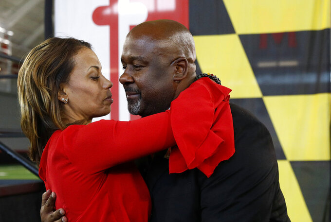 Maryland's new head football coach Mike Locksley, right, embraces his wife Kia after an NCAA college football news conference, Thursday, Dec. 6, 2018, in College Park, Md. Locksley, Alabama's offensive coordinator, will take over at Maryland after the most tumultuous year in the program's recent history. (AP Photo/Patrick Semansky)