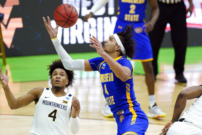 Morehead State's Johni Broome, right, reaches a rebound before West Virginia's Miles McBride, left, during the first half of a college basketball game in the first round of the NCAA tournament at Lucas Oil Stadium Friday, March 19, 2021, in Indianapolis. (AP Photo/Mark Humphrey)