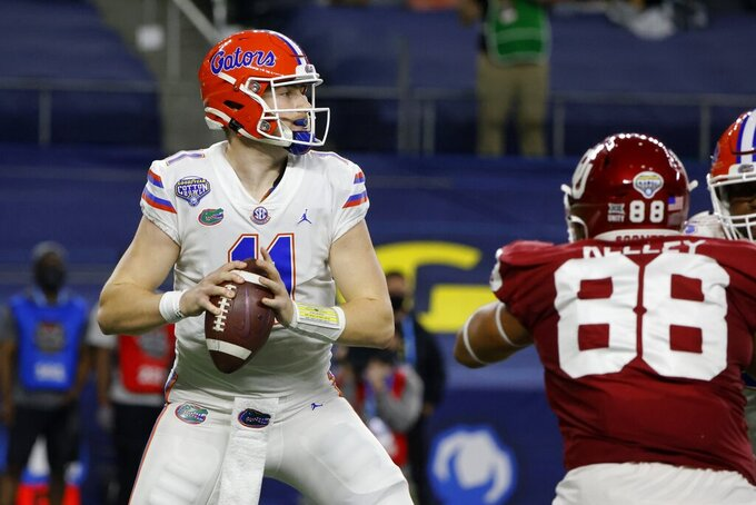 Florida quarterback Kyle Trask (11) drops back to pass under pressure from Oklahoma defensive lineman Jordan Kelley (88) during the first half of the Cotton Bowl NCAA college football game in Arlington, Texas, Wednesday, Dec. 30, 2020. (AP Photo/Michael Ainsworth)