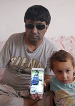 In this Saturday, June 7, 2018 photo, Abdul Agha, 33, a former policeman who lost his right arm and both eyes when his convoy hit a roadside bomb three years ago, shows a photo from before his wounds during an interview with The Associated Press at his house in Kabul, Afghanistan. Peace in Afghanistan seems even more elusive, both for troops on the front lines of this war-battered country and for survivors of countless attacks, since the Taliban shrugged off the government's latest offers of cease-fire and negotiations. (AP Photo/Massoud Hossaini)