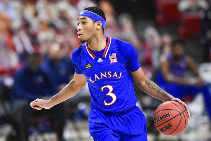 Kansas' Dajuan Harris (3) controls the ball during the first half of an NCAA college basketball game against Texas Tech in Lubbock, Texas, Thursday, Dec. 17, 2020. (AP Photo/Justin Rex)