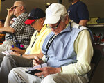 FILE - In this March 5, 2016, file photo, Tommy Giordano, right, special assistant to the general manager of the Atlanta Braves, scouts a spring training baseball game between the Braves and the Pittsburgh Pirates, in Kissimmee, Fla. Giordano spent nearly all of his marvelously full life as a baseball man. He was a major league player (for 11 games with the late, great Philadelphia Athletics), a minor-league manager, a front-office executive. More than anything, he was a scout, one of those guys who combed the backwoods and backwaters searching for the game's next big star. (AP Photo/Paul Newberry, File)