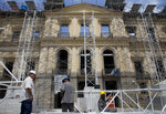 Workers erect scaffolding in front of Brazil's National Museum, in Rio de Janeiro, Brazil, Tuesday, Feb. 12, 2019. Five months after a devastating fire engulfed Brazil's National Museum, the facility is still in dire straits and efforts to rebuild slow-moving. (AP Photo/Silvia Izquierdo)