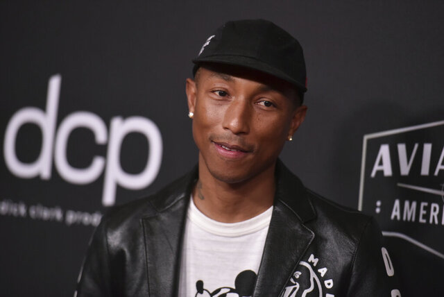 """FILE - In this Nov. 3, 2019 file photo, Pharrell Williams arrives at the 23rd annual Hollywood Film Awards at the Beverly Hilton Hotel in Beverly Hills, Calif.  Virginia Beach is considering painting Black Lives Matter down its oceanfront boardwalk after Williams supported the idea on social media.  Williams proposed the tribute in an Instagram post adding a photo of what the message would look like along Virginia Beach's boardwalk with the caption """"VB let's make it happen."""" (Photo by Richard Shotwell/Invision/AP)"""