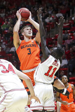 Oregon State forward Tres Tinkle (3) looks over the arms of Utah forward Both Gach (11) while shooting during the first half of an NCAA college basketball game Saturday, Feb. 2, 2019, in Salt Lake City. (AP Photo/Chris Nicoll)