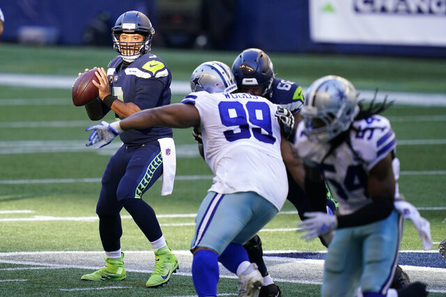 Seattle Seahawks quarterback Russell Wilson, left, looks to pass against the Dallas Cowboys during the second half of an NFL football game, Sunday, Sept. 27, 2020, in Seattle. (AP Photo/Elaine Thompson)