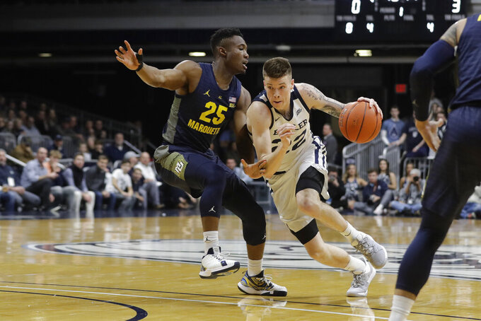 Butler's Sean McDermott (22) goes to the basket against Marquette's Koby McEwen (25) during the first half of an NCAA college basketball game, Friday, Jan. 24, 2020, in Indianapolis. (AP Photo/Darron Cummings)