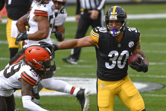 Pittsburgh Steelers running back James Conner (30) eludes Cleveland Browns safety Sheldrick Redwine (29) during the first half of an NFL football game, Sunday, Oct. 18, 2020, in Pittsburgh. (AP Photo/Don Wright)