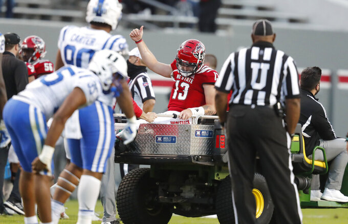 North Carolina State quarterback Devin Leary (13) gives a thumbs-up as he is taken off the field after being injured during the second half of an NCAA college football game against Duke in Raleigh, N.C., Saturday, Oct. 17, 2020. (Ethan Hyman/The News & Observer via AP)