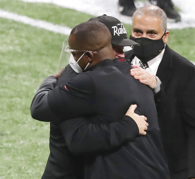 Atlanta Falcons head coach Raheem Morris, left, and Las Vegas Raiders head coach Jon Gruden greet each other with a hug after the Falcons defeated the Raiders in an NFL football game on Sunday, Nov 29, 2020, in Atlanta. (Curtis Compton/Atlanta Journal-Constitution via AP)