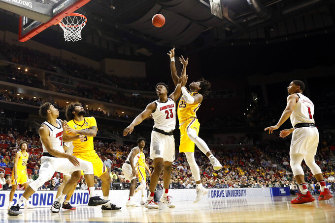 Minnesota center Daniel Oturu (25) shoots over Louisville center Steven Enoch (23) during a first round men's college basketball game in the NCAA Tournament, Thursday, March 21, 2019, in Des Moines, Iowa. (AP Photo/Charlie Neibergall)