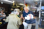 """Owner Richard Ravenscroft talks with patrons as he leaves for a delivery order at the Coney Market, which sold the winning ticket, Tuesday, June 15, 2021, in Lonaconing, Md. Sometime in late January, someone bought a Powerball lottery ticket at the Coney Market, and that ticket's six numbers won the big one — $731 million, the biggest jackpot ever in Maryland and the fifth-richest payout in U.S. history. """"We'll find out who the winners are,"""" the shopkeeper says, """"when they quietly move away."""" (Jabin Botsford/The Washington Post via AP)"""