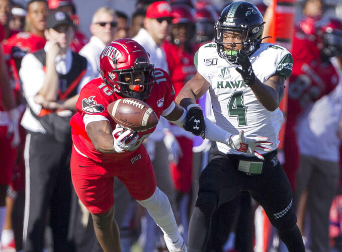 UNLV wide receiver Darren Woods Jr. (10) tries to make a catch with Hawaii defensive back Rojesterman Farris II (4) in pursuit in the first quarter of an NCAA college football game Saturday, Nov. 16, 2019, in Las Vegas. (Benjamin Hager/Las Vegas Review-Journal via AP)