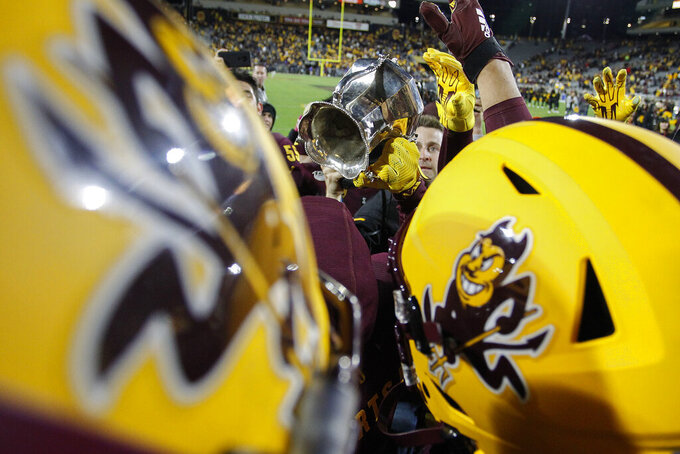 Arizona State players hold up the Territorial Cup after their 24-14 win over Arizona during their NCAA college football game Saturday, Nov. 30, 2019, in Tempe, Ariz. (AP Photo/Darryl Webb)