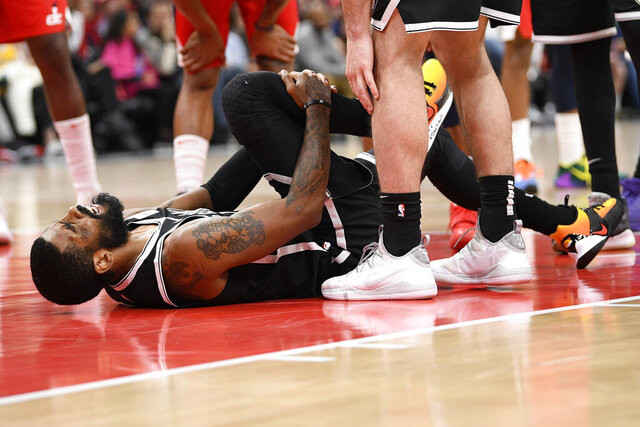 Brooklyn Nets guard Kyrie Irving grabs his leg after he was injured during the second half of an NBA basketball game against the Washington Wizards, Saturday, Feb. 1, 2020, in Washington. (AP Photo/Nick Wass)