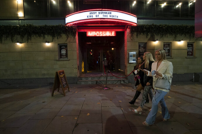 Members of the public walk through central Manchester, England, Thursday Oct. 22, 2020, as strict coronavirus restrictions on England's second-largest urban area, Greater Manchester, will start at midnight. (AP Photo/Jon Super)