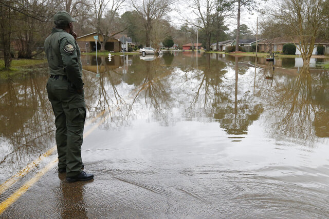A Mississippi Department of Wildlife, Fisheries and Parks lawman, observes the swirling Pearl River floodwaters drain from North Canton Club Circle in Jackson, Miss., Tuesday afternoon, Feb. 18, 2020. Officials have limited entry to the flooded neighborhoods as they have warned residents about the contamination of the receding waters and the swift currents. (AP Photo/Rogelio V. Solis)