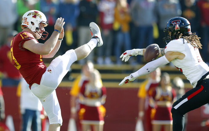 Texas Tech defensive back Thomas Leggett blocks a punt by Iowa State punter Corey Dunn, left, during the first half of an NCAA college football game, Saturday, Oct. 27, 2018, in Ames, Iowa. Leggett recovered the block in the end zone for a Texas Tech touchdown. (AP Photo/Charlie Neibergall)