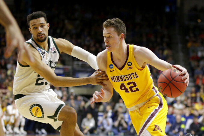 Minnesota's Michael Hurt (42) drives against Michigan State's Kenny Goins, left, during the first half of a second round men's college basketball game in the NCAA Tournament, in Des Moines, Iowa, Saturday, March 23, 2019. (AP Photo/Nati Harnik)