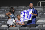 A disappointed fan holds a sign calling for the firing of Dave Gettleman, senior vice president of the New York Giants, after their defeat against the Atlanta Falcons after an NFL football game, Sunday, Sept. 26, 2021, in East Rutherford, N.J. (AP Photo/Bill Kostroun)