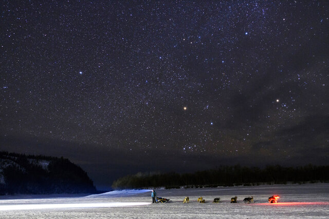 FILE - In this March 9, 2019 file photo Kristy Berington waits on the Innoko River for her sister, Anna Berington, after they both left Shageluk, Alaska, during the Iditarod Trail Sled Dog Race. Nearly 1,000 miles (1,600 kilometers) of unforgiving terrain, doused in deep snow this year, await them as they cross two mountain ranges, travel on the frozen Yukon River and navigate the treacherous and wind-whipped Bering Sea coast to old Gold Rush town of Nome. The winner is expected there about 10 or 11 days after the start. (Marc Lester/Anchorage Daily News via AP,File)