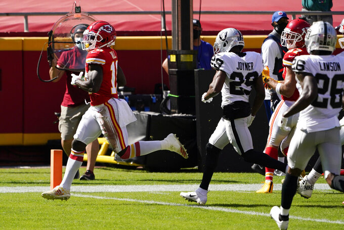 Kansas City Chiefs wide receiver Tyreek Hill (10) scores on a 10-yard touchdown run ahead of Las Vegas Raiders safety Lamarcus Joyner (29) during the first half of an NFL football game, Sunday, Oct. 11, 2020, in Kansas City. (AP Photo/Jeff Roberson)