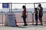 People wearing protective face masks stand at a closed entrance to the beach during the new coronavirus pandemic, Friday, July 3, 2020, in the South Beach neighborhood of Miami Beach, Fla. Beaches throughout South Florida are closed for the busy Fourth of July weekend to avoid further spread of the new coronavirus. (AP Photo/Lynne Sladky)