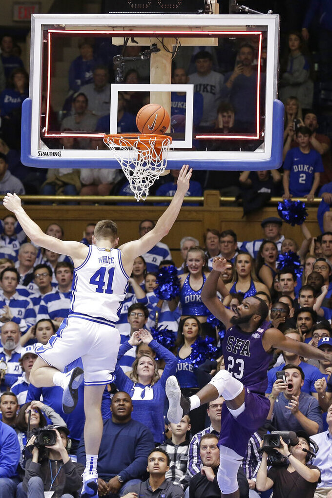 Stephen F. Austin forward Nathan Bain (23) watches the game winning basket fall as Duke forward Jack White (41) defends during overtime in an NCAA college basketball game in Durham, N.C., Tuesday, Nov. 26, 2019. Stephen F. Austin won 85-83. (AP Photo/Gerry Broome)