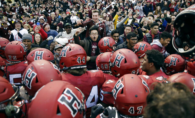 FILE - In this Nov. 17, 2018, file photo, Harvard players, students and fans celebrate the team's win over Yale in an NCAA college football game at Fenway Park in Boston. The Ivy League was the first Division I conference to suspend fall sports in 2020 because of the COVID-19 virus outbreak. All eight Ivies are requiring that their football teams be vaccinated for COVID-19 — just like the rest of the students on campus. (AP Photo/Charles Krupa, File)