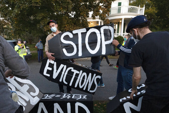FILE - In this Oct. 14, 2020, file photo, housing activists erect a sign in front of Massachusetts Gov. Charlie Baker's house in Swampscott, Mass. A federal judge has ruled, Wednesday, May 5, 2021, that the Centers for Disease Control exceeded its authority when it imposed a federal eviction moratorium to provide protection for renters out of concern that having families lose their homes and move into shelters or share crowded conditions with relatives or friends during the pandemic would further spread the highly contagious virus. (AP Photo/Michael Dwyer, File)