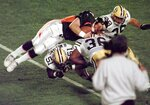 File-This Jan. 25, 1998, file photo shows Denver Broncos quarterback John Elway being flipped by Green Bay Packers' Brian Williams (51) and Elroy Butler (36) for a first down during Super Bowl XXXII at Qualcomm Stadium in San Diego. Members of a special panel of 26 selected all of them for the position as part of the NFL's celebration of its 100th season. All won league titles except Marino. All are in the Hall of Fame except Brady and Manning, who are not yet eligible.  On Friday, Dec. 27, 2019, quarterback was the final position revealed for the All-Time Team.  (AP Photo/Elaine Thompson, File)