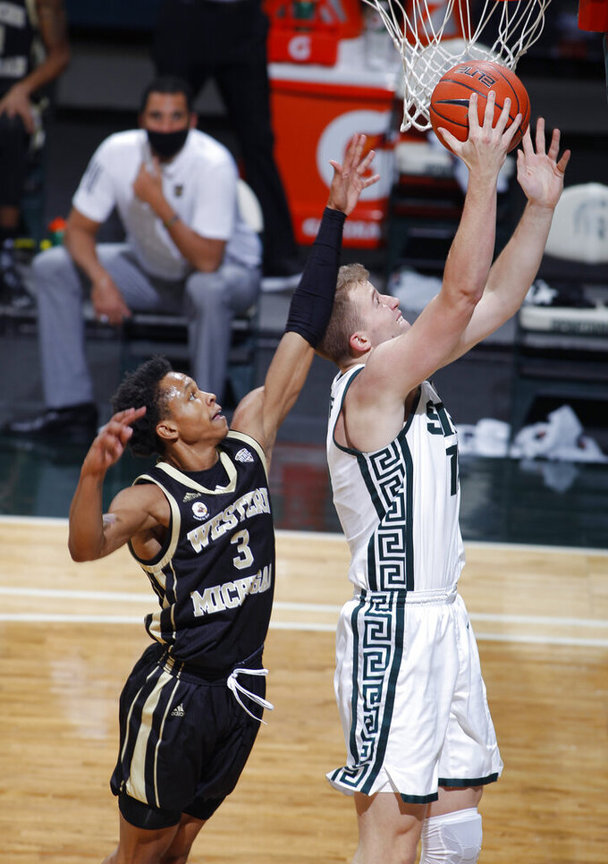 Michigan State's Thomas Kithier, right, goes up for a layup against Western Michigan's B Artis White during the first half of an NCAA college basketball game, Sunday, Dec. 6, 2020, in East Lansing, Mich. (AP Photo/Al Goldis)